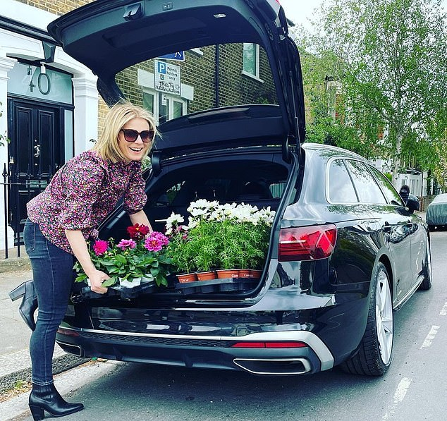 Emilia Fox, 46, shared a photo of herself carrying pink dahlias and white cosmos from the trunk of her car