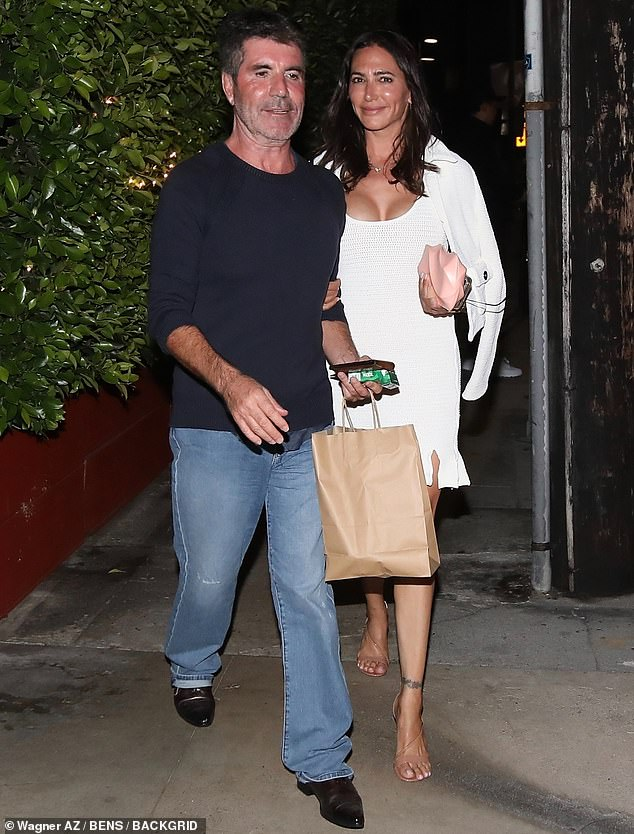 All smiles: The couple showed off their sun-kissed skin after dinner as the producer flaunted a smile in jeans and a black sweater with brown dress shoes