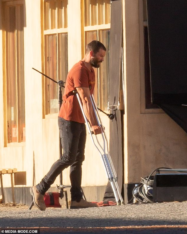What's happened to Christian Grey? Fifty Shades Of Grey star Jamie Dornan looked worse for wear as he sported a nasty head wound and hobbled around on crutches on the set of The Tourist in the Australian outback on Tuesday