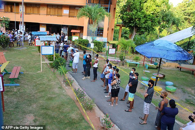 The new measures will also include a ban on mixing of households, certain types of gatherings and the early closure of shops, bars and casinos.  Non-essential workers are also encouraged to work from home and an 23-hour curfew will remain in place.  Pictured: People wearing masks line up to vote in the country's presidential elections last year [file photo]