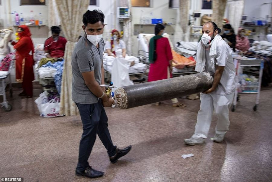 Relatives of a woman suffering from Covid fetch an oxygen tank to help her breathe at a hospital in Delhi amid the country's virus crisis