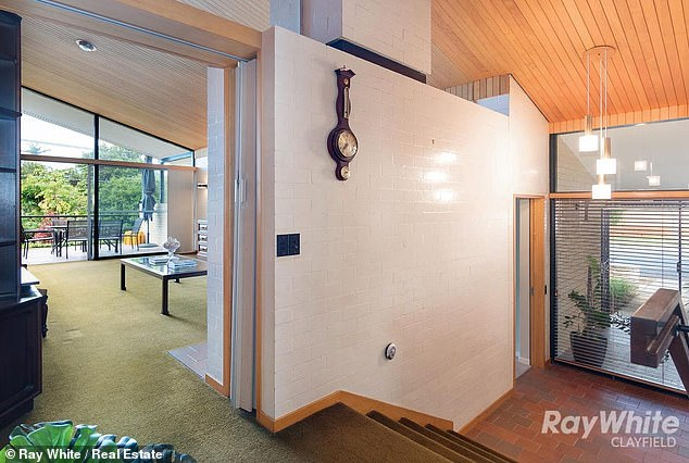 Modernist features remaining in the home include floor to ceiling glass and silver ash ceilings