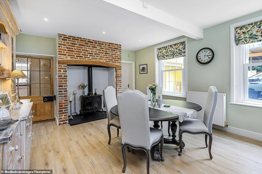 The home's kitchen-diner boasts a wood burner and old brick fireplace and has plenty of space for a good-size table