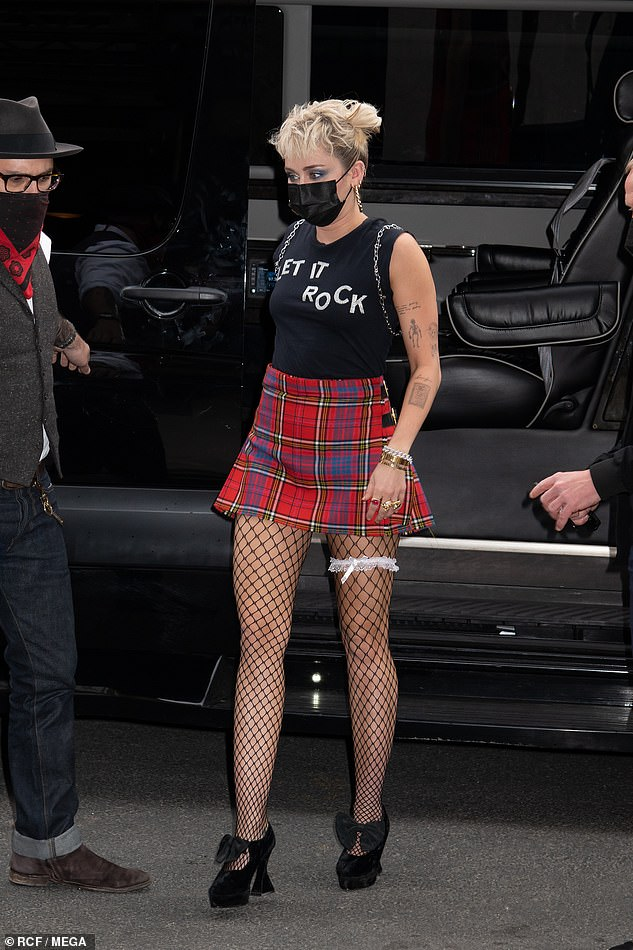 Fashion statement: She had on a black 'Let it rock' tank top and stepped out in towering black platform shoes with bows on the top
