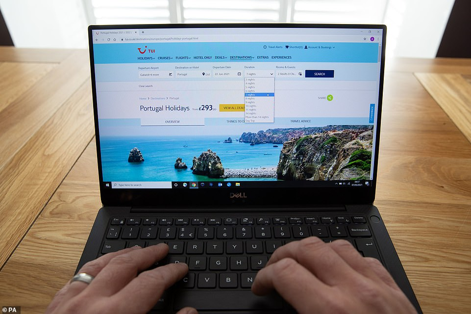 A person browses a web page for summer holidays to Portugal on the Tui website today ahead of the announcement later