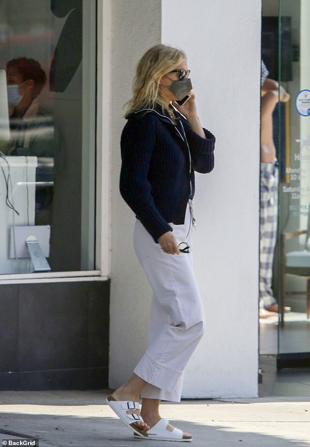 Easy breezy: The Oscar winner, 48, strolled along on the sidewalk in white Birkenstock-style sandals, paired with matching wide-legged white trousers that were cuffed above her ankles
