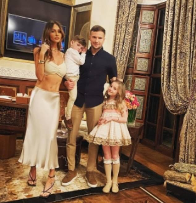 So sweet:In the photo, Georgina's husband Tom, 31, and their two other children - Albie and Nevaeh - put their hands on her growing tummy (pictured together in February)