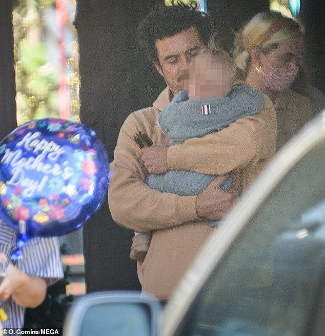 Baby to me: Orlando Bloom was spotted lovingly rocking his baby girl Daisy on her travels this weekend