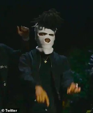 Explicit: In the video, he dons a white ski mask and waves a gun as he performs the curse-laden hook