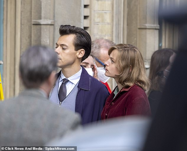 Film: Members of the team could be seen nearby sorting out face masks while extras wearing old-fashioned clothes were also seen walking by Harry and Emma