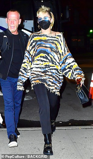 Finishing touches: Miley added to her look with cropped pants, while stylish black leather boots and a matching handbag complete things