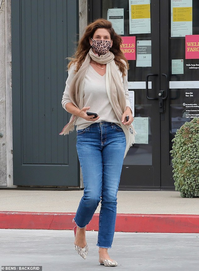 Eye contact:The runway star, 55, cut a chic and casual figure, in a putty-colored V-neck sweater and form-fitting denim blue jeans
