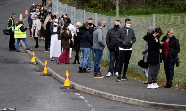 People line up outside a mobile vaccination centre in Bolton, where coronavirus cases have almost doubled in a week