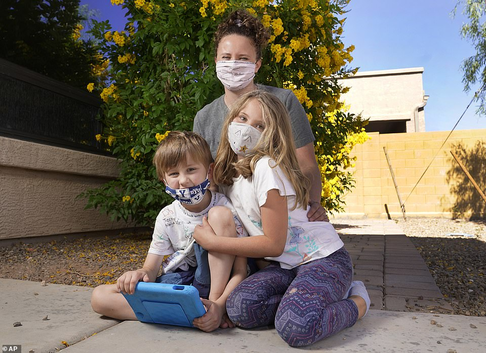 While many parents are for getting risk of mask mandates, many are also in favor of keeping them, including Christie Back of Mesa, Arizona. Pictured: Black with her two children, Luke (left) and Angela (right) in front of their home, May 11