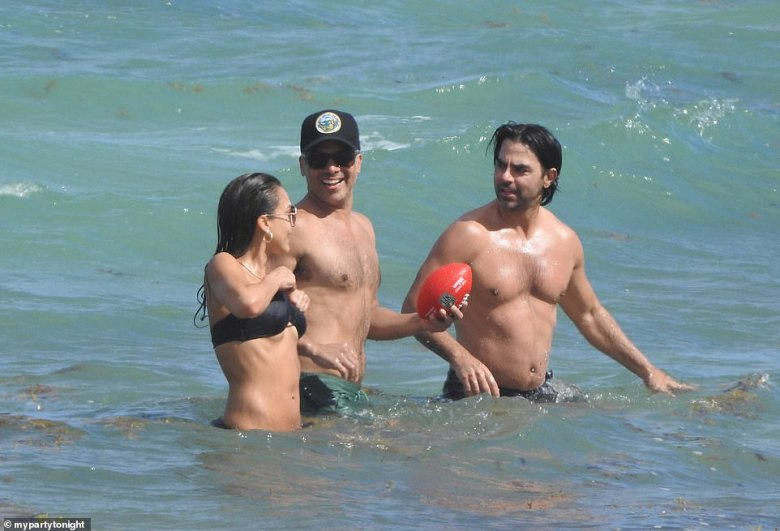 Alba appeared to be all smiles as she frolicked in the waves and played football with her hubby and a male friend