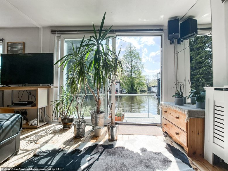 The living area in the floating houseon the edge of Royal Park in Hampton, near Twickenham, which features patio doors that open onto the deck.Taggs Island, where the houseboat is located, has just over 100 residents