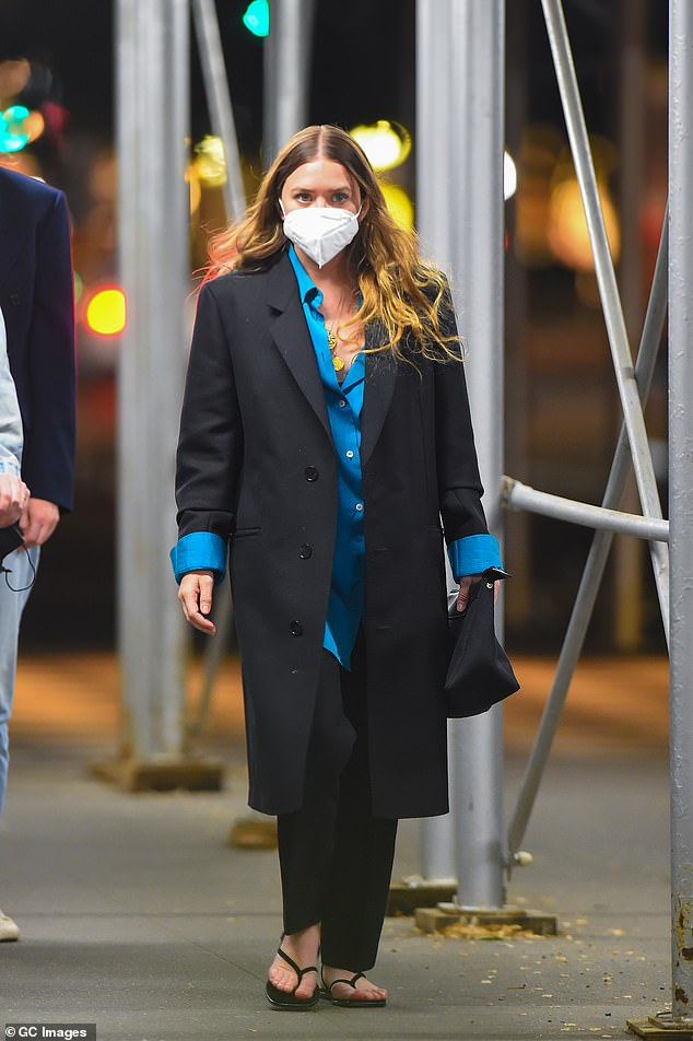 Style:The fashion designer, 34, donned a smart black longline coat worn over an oversized bright blue shirt as she made her way down the street following her meal