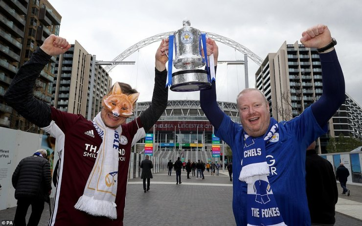 Leicester fans wearing fox masks and holding replica FA Cup trophies pose for pictures on Wembley Way