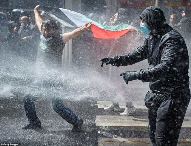Marches in support of Palestinians in the Gaza Strip were also held today in a dozen French cities, but the focus was on Paris, where riot police got ready as organizers said they would defy a ban on the protest. Pictured, Protesters face water cannons in Paris on Saturday