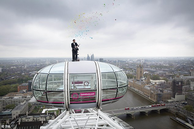 Sunny Jouhal, general manager of the lastminute.com London Eye, stands on top of a London Eye pod to celebrate the re-opening of the attraction today
