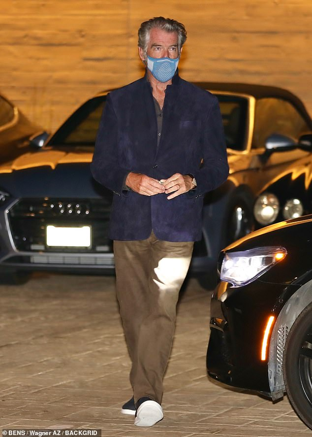 Beau: Pierce put on a dapper display for the outing by teaming a dark blue suit jacket with an open-neck shirt