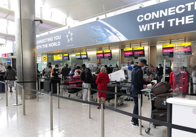Airline staff help passengers check-in in the departures hall at London Heathrow Airport's Terminal 2 yesterday
