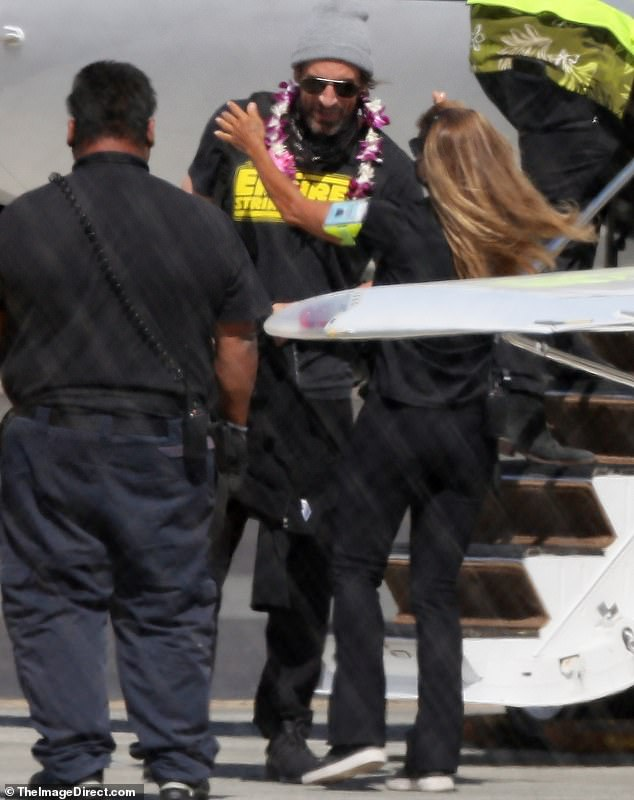 He's leaving: the two were decked out in leis as they emerged from the plane and crossed the sunny tarmac