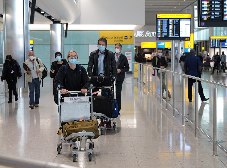 Air passengers arrive at London Heathrow as they wear face masks while walking through the arrivals hall
