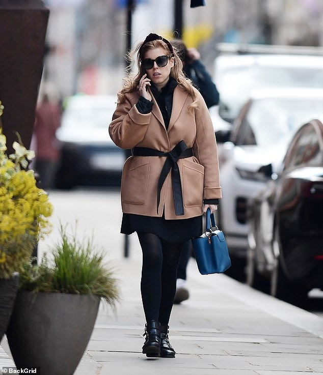 A rather windswept Princess wore a warm brown coat with a black tie up belt, a stylish blue Louis Vuitton Handbag with dark sunglasses as she chatted away on her phone out in Mayfair on May 4