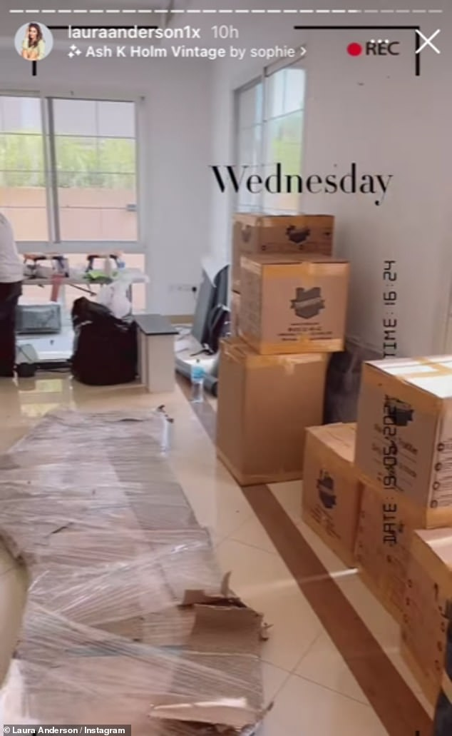 Moving day: There were cardboard boxes bearing a specific black logo stacked up in the corner as well as packages wrapped in black with brown tape as she packed up