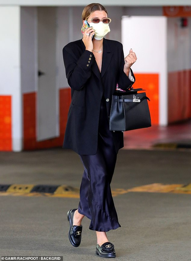 Elegant:Underneath her classic black blazer, she donned a flowing ankle-length navy blue satin dress that clung to her long legs as she strolled