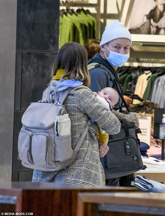 Doting: Todd strapped a baby carrier around his chest and also toted a number of bags and even a knitted blanket for Lion