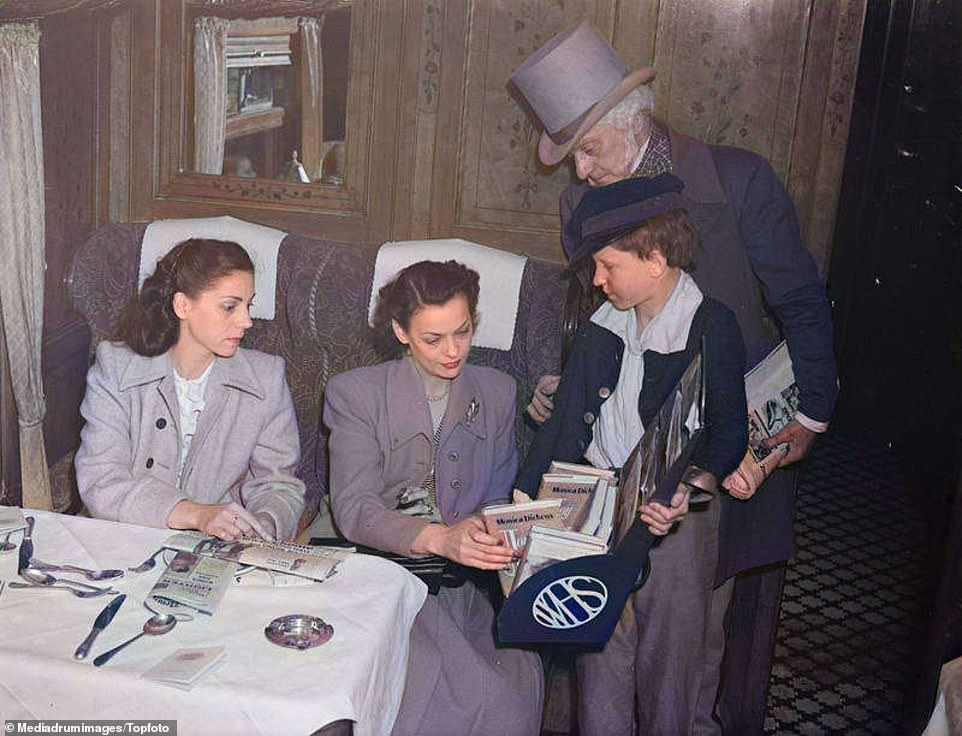 In this picture taken on August 30, 1948, passengers Miss Dorothy (left) and Rosalie Edwards of Portman Square, London, buy magazines from 11-year-old Fred Edwards (no relation) of Euston. Dressed in the newsboy style of Charles Dickens' time, Fred is deputising for John Howard Davies, the boy 'star' of the Oliver Twist film