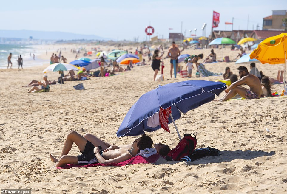 Holidaymakers enjoy the sunshine on Faro beach, Portugal on the first day of the easing of restrictions for International travel