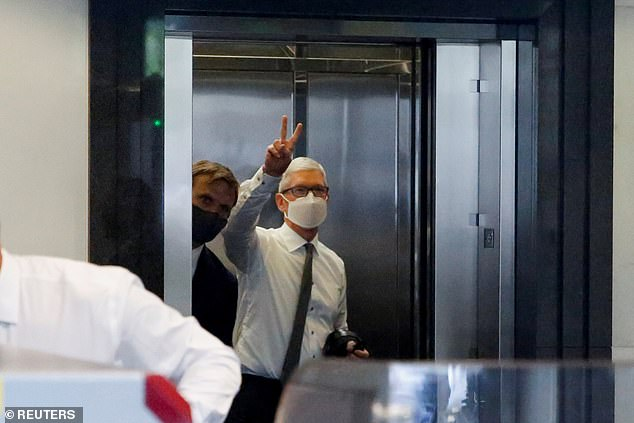 Apple CEO Tim Cook gestures from the elevator as he arrives in court on Friday to testify at the conclusion of a weeks-long antitrust trial