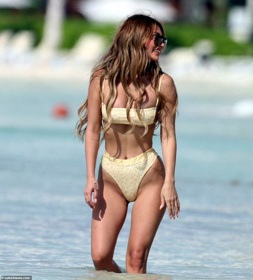 Killer frame:Her statuesque legs and tiny waist were offset by her perky bust which peaked out of her bandeau swimsuit