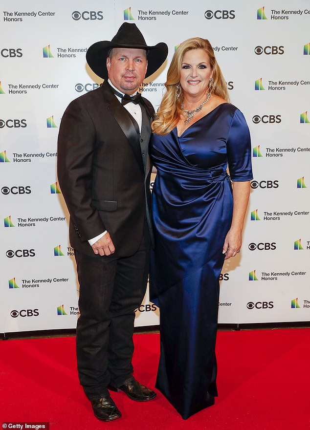 Blue mood:He was accompanied by his wife and fellow country superstar Trisha Yearwood, who shimmered in a navy blue satin dress that was ruched around her midriff