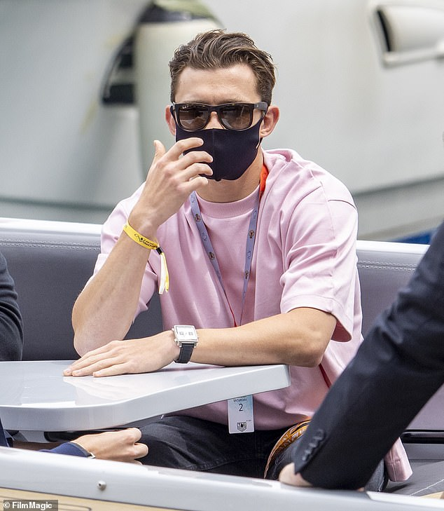 Fun: The actor cut a casual figure in a pink T-shirt and black jeans as he spent the day chatting to friends on a boat and visiting the pit lane