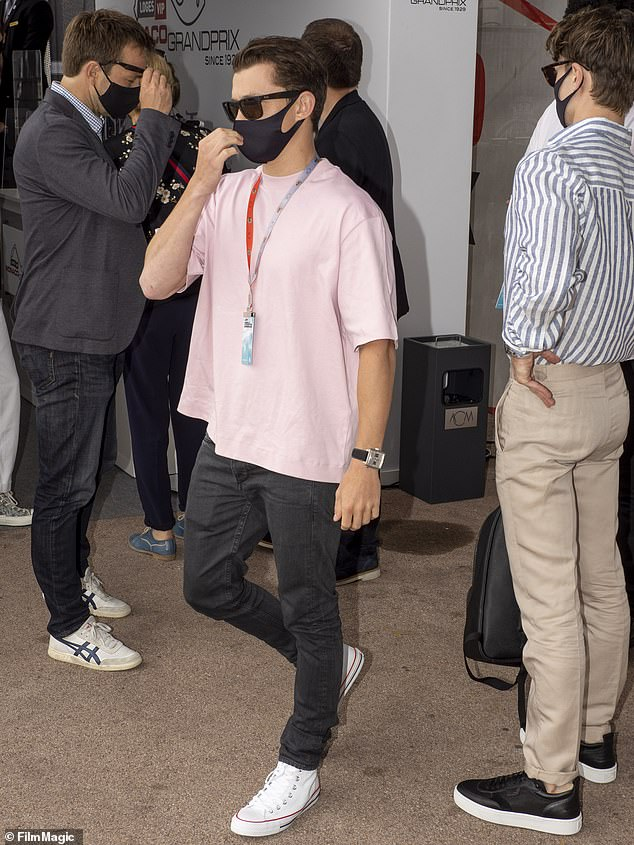 Best foot forward: Tom completed his laidback look with a pair of white converses with signature red details
