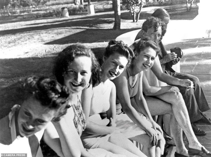 Shortly after celebrating her 21st birthday, during her first overseas tour with her parents, hundreds looked on as the Queen swam off the South African coast. A reporter's description of her in her bathing costume (pictured, fourth from left) as having 'curves in all the right places' is said to have marred her father's enjoyment of the visit