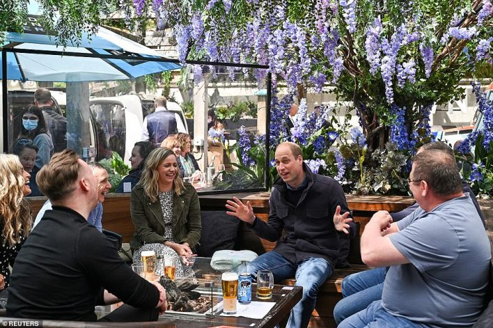 The Duke appeared to be engaged in an animated conversation with the group, all of whom were laughing as they listened to him