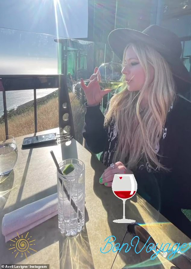 Her comes the sun: Lavigne took nice sip of her wine as she soaked in the sunshine