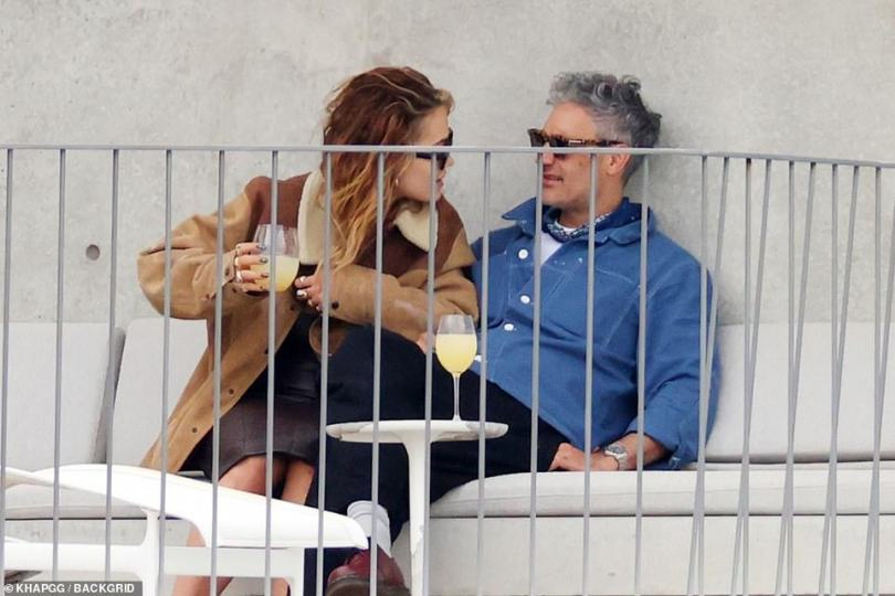 Eh? Taika looked a little confused as he chatted to his girlfriend on the cream outside sofa