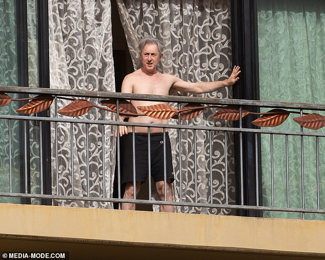 Quarantine chic: He stepped out in just a pair of black shorts slung low on his hips, and his grey hair appeared slightly dishevelled