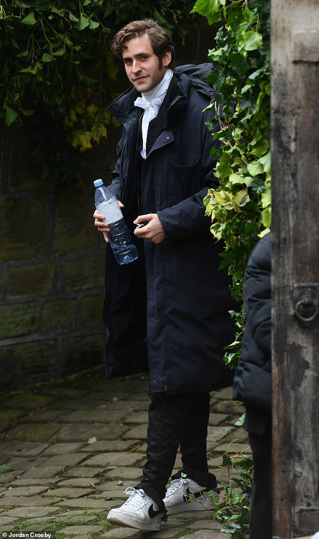 Outfit: Oliverwas dressed up in a black suit that he paired with a white shirt, and in between takes he also donned a blue padded coat