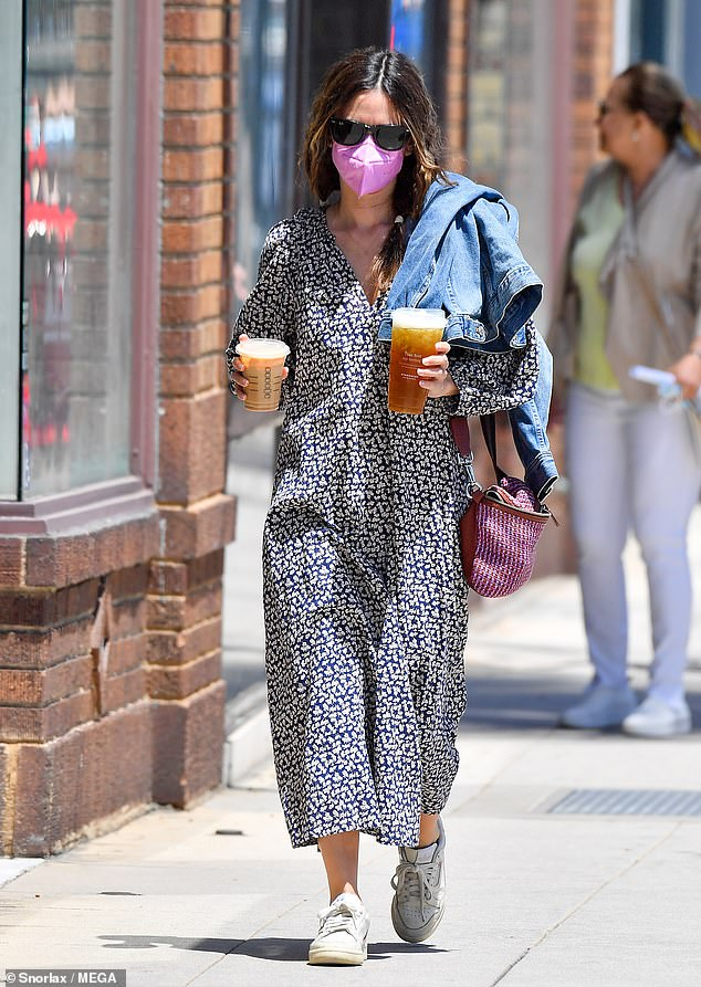 Hands full: The 39-year-old LA native had a jean jacket slung over her shoulder and she was wearing a pink face mask, which is still required inside businesses