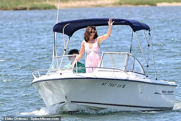 Like a royal: Luann had fun waving to fans as her man took the wheel of the boat