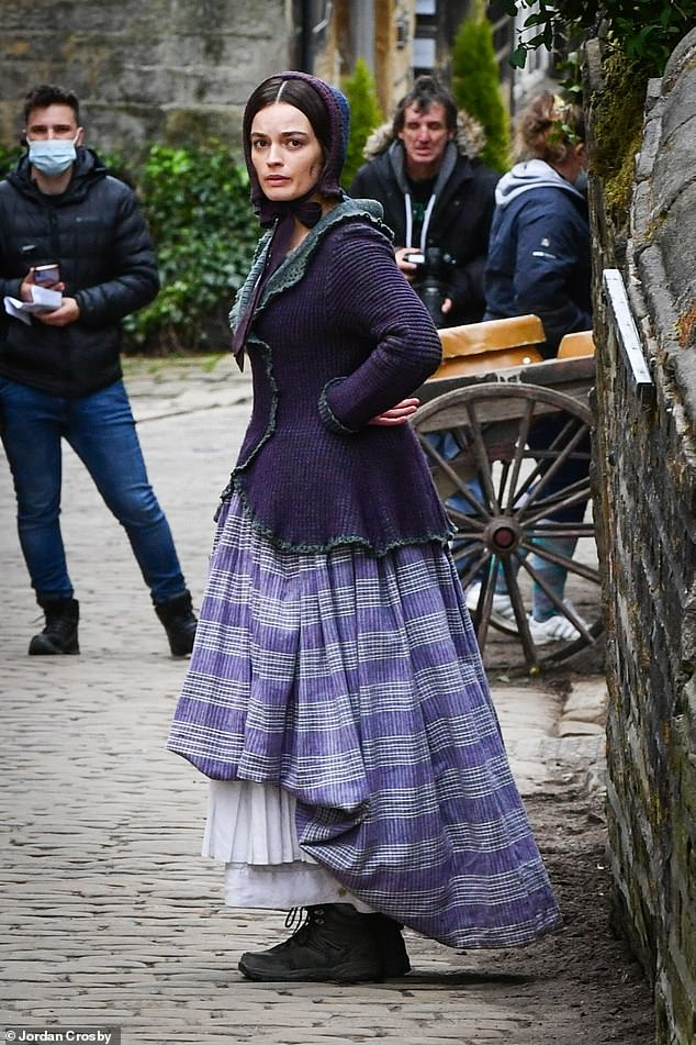 Different look: Emma transformed into her new part perfectly with the purple dress and matching bonnet