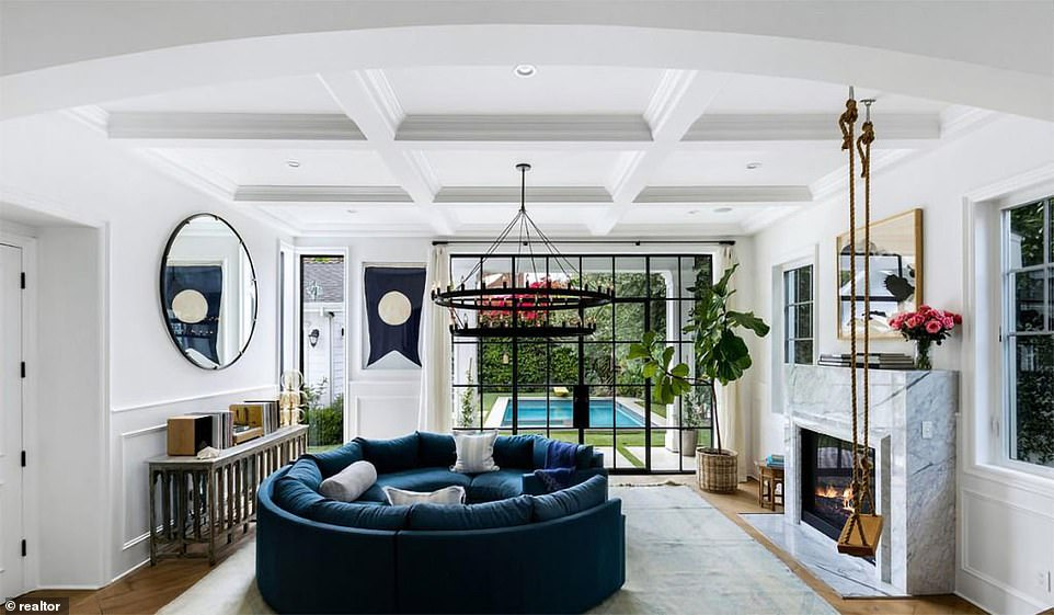 The living room adjoining the foyer has a marble fireplace and steel and glass doors that open onto the small backyard