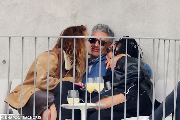 Close:In pictures obtained exclusively by MailOnline, the trio appeared to be in great spirits as they wrapped their arms around each other and beamed smiles over al fresco drinks